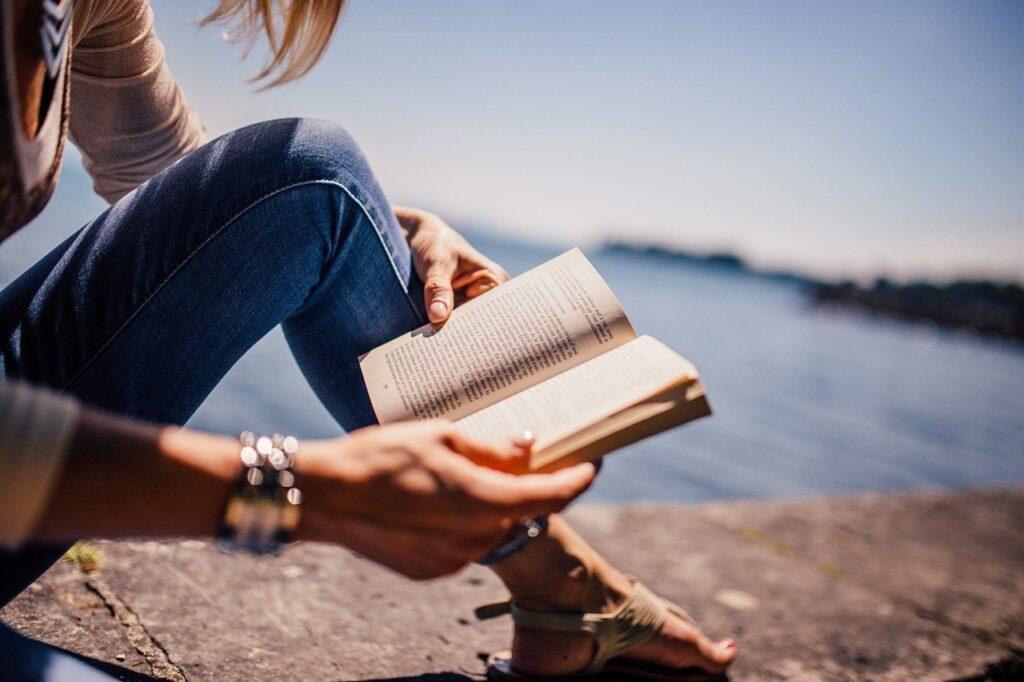 Romanzo Oblio, lettrice con romanzo al mare